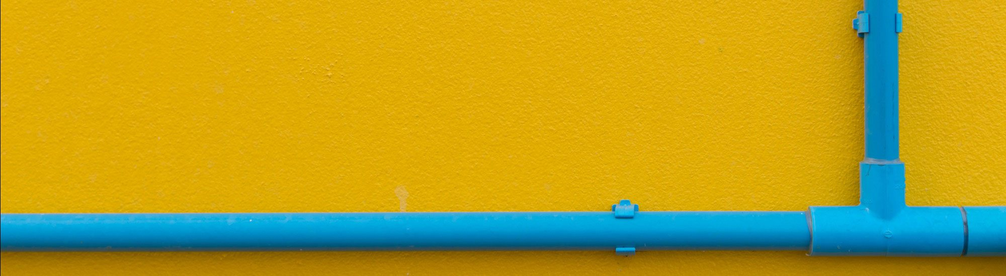 blue pipes over yellow wall